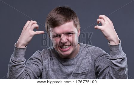 Furious blond young man on gray background