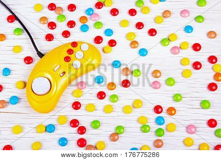 Yellow retro gamepad on a background of chocolate colored pills. Video game console GamePad on a white wooden table.