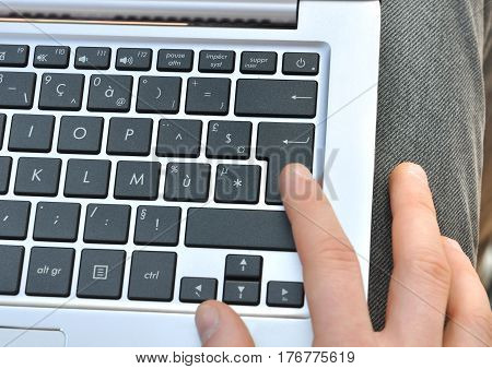 finger on entry key of a laptop on a young man keens