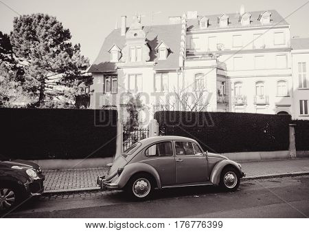 STRASBOURG FRANCE - 25 DEC 2016: Black and white retro image of a vintage classic Volkswagen Beetle car on the street of Strasbourg France with beautiful houses real estate in the background