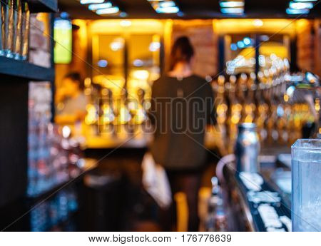 Silhouette of sexy bartender barmaid working in bar - defocused silhouette of bar atmosphere and lights