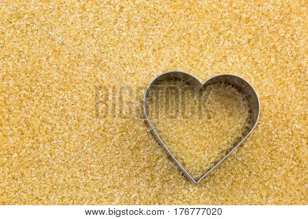 Top view of Metal heart shaped cookie cutter on unrefined unbleached Crystalline sugar in crystal brown color with copyspace. Conceptual photo for sweet love