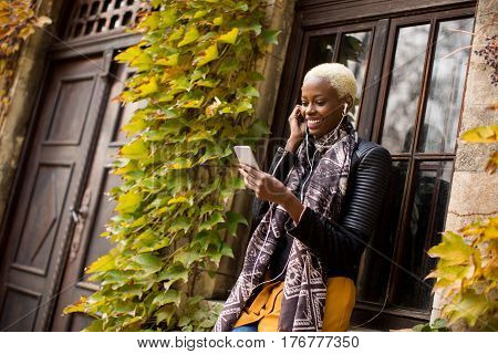 Pretty young african american woman with smartphone outdoor