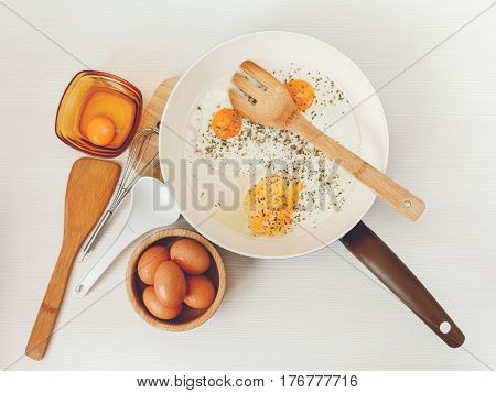 Fried eggs in the frying pan,breakfast ingredients,kitchen accessories.Fresh Brown Eggs in the Wooden Plate.Cooking morning food.White Background.Top View