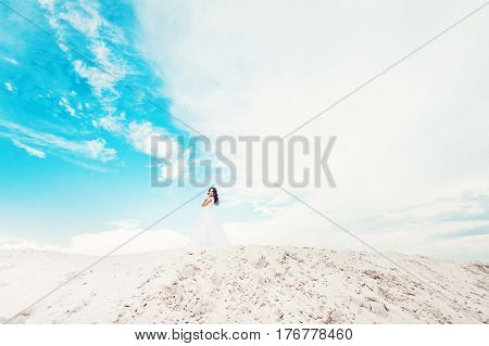 Young smiling brunette woman running in fashionable lace wedding dress against the blue summer sky on her wedding day. portrait of beautiful bride with long brown curly hair on the beach