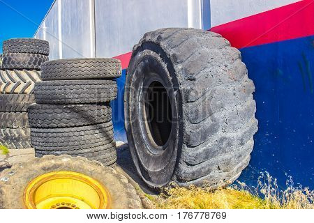 Giant Tire & Other Tire Stacks Against Building Sid