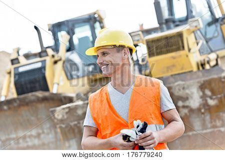 Happy supervisor looking away at construction site
