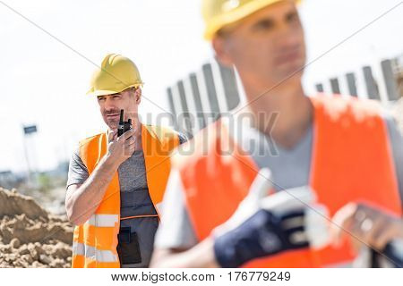 Middle-aged male worker using walkie-talkie with colleague in foreground at construction site