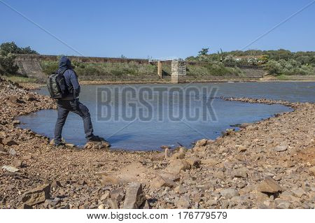 Man overlooking the Roman Dam of Cornalvo. This dam was declared National Monument on Dec 13th 1912 and it is still in use nowadays