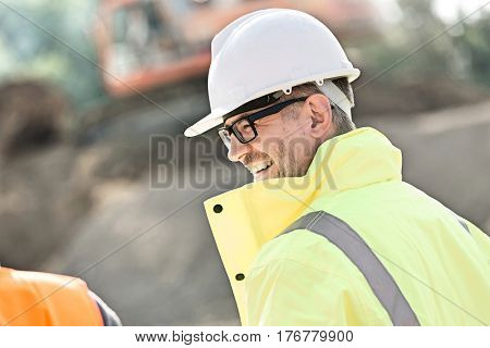 Side view of happy male supervisor at construction site