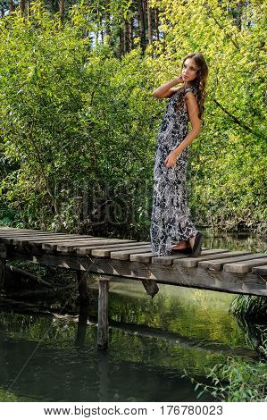 Attractive young woman stands on a wooden bridge outdoors