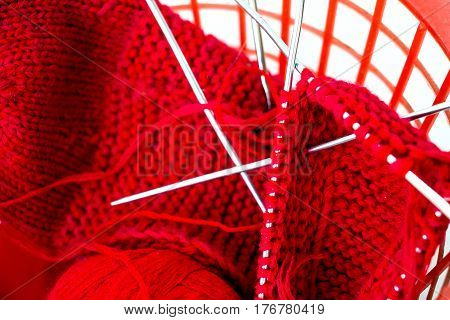 Knitting needles, a red woolen thread in a tangle and needlework