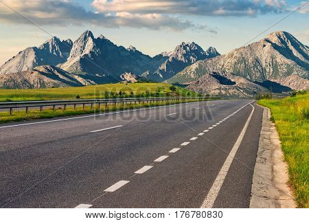 Travel destination concept image. Composite landscape of High Tatra mountain ridge. Straight asphalt highway through green hills leads to high peaks.
