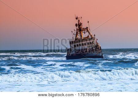 Shipwreck in wild Atlantic Ocean at Skeleton Coast, Namibia, Africa.