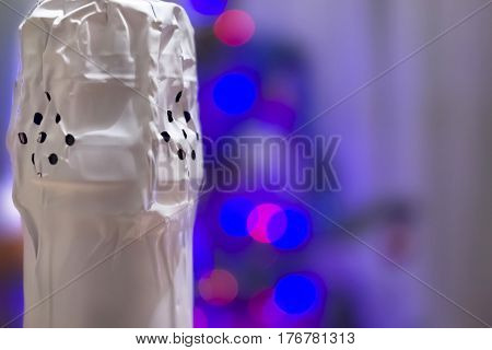 Corked neck of a bottle of champagne close-up against the backdrop of a New Year's bokeh