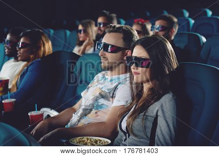 Couple sitting in modern and comfortable cinema hall and watching movie. Handsome boyfriend and brunette girlfriend wearing in 3d glasses, seriously looking at projector.