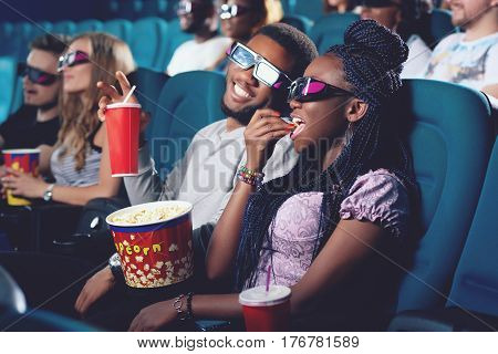 Positive couple of africans spending free time in cinema together. Girlfriend and boyfriend in 3d glasses sitting in modern cinema hall eating popcorn, drinking cola and watching funny movie.