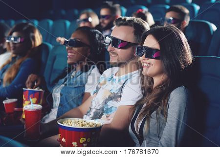 Side view of smiling brunette holding popcorn and looking at projector. Group of friends  watching movie in modern cinema hall and smiling together.