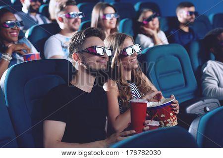 Positive couple drinking cola and eating popcorn when looking at project. Smiling couple of boyfriend and gifrliend embracing in cinema and watching funny movie. Group of africans on background.
