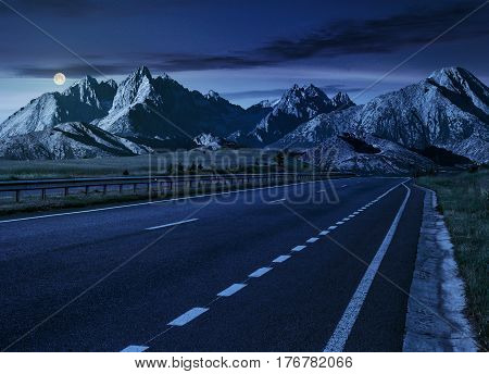 Travel destination concept image. Composite landscape of High Tatra mountain ridge at night in full moon light. Straight asphalt highway through green hills leads to high peaks.