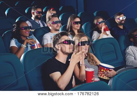 Boyfriend and gifrliend sitting in modern cinema hall, watching funny movie and emotionally gesturing by hands. Positive couple wearing in 3d glasses drinking cola and eating popcorn.