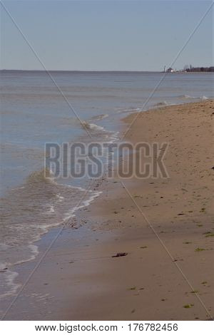 A look at the bay with sand and small waves