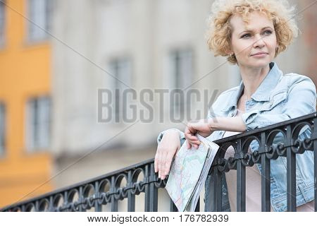 Thoughtful middle-aged woman holding map while leaning on railing