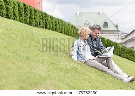 Middle-aged couple reading map while sitting at park