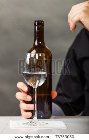 Liqour alcohol party dinner bartending concept. Cup and bottle on table. Wine in glass held by human hand.