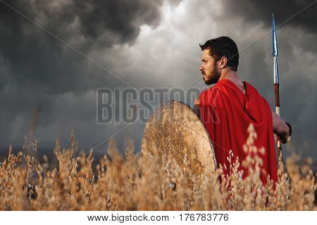 Back view of warrior with beard wearing like spartan looking away over shoulder. Brunet soldier going in attack with bronze rounded shield and weapon. Dark clouds in sky and bad weather. War in field.