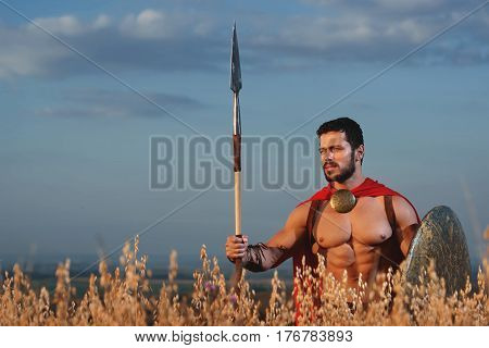Portrait of handsome brunet soldier with beard in red cloak wearing like spartan holding iron weapon in hands. Warrior with bare torso going in attack with rounded shield. War in field.