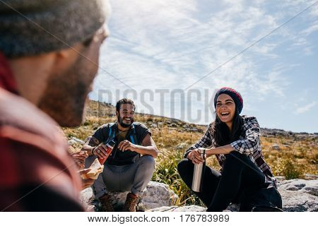 Group of people taking a break relaxing during a hike. Young woman with friends taking a break during a hike in countryside.
