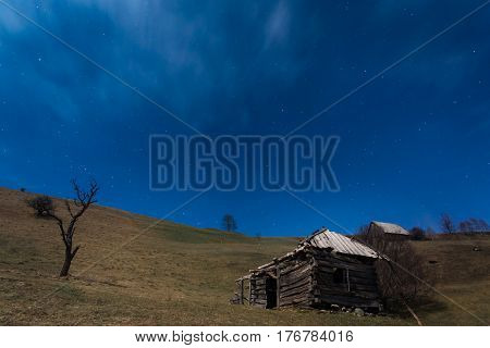 Shattered wooden cottage on top of the hill under the blue sky with lots of stars. Night landscape in Carpathians Romania
