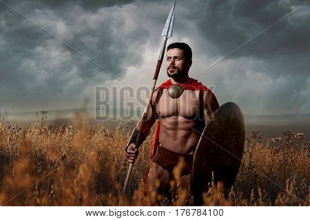 Athletic and handsome warrior with beard in red cloak with sword and shield going in attack. Soldier with bare torso like spartan or antique roman looking away. Dark sky over field.