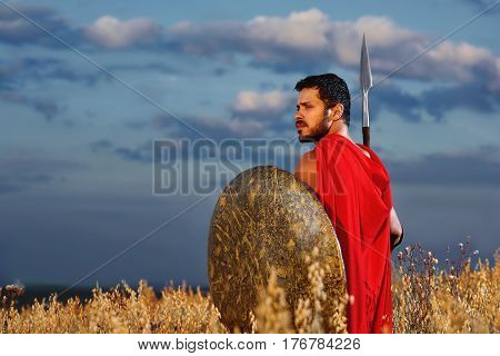 Back view of warrior with beard wearing in red cloak holding sword and looking away over shoulder. Brunet male like spartan or antique roman with iron weapon before the battle. Dark clouds.