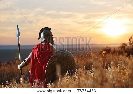 Incognito warrior in iron helmet and red cloak holding sword and looking at horizon. Male like spartan or antique roman with iron weapon before the battle. Sunset in field.