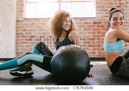 Two happy young women sitting on gym floor with medicine ball. Female friends taking a break from workout.