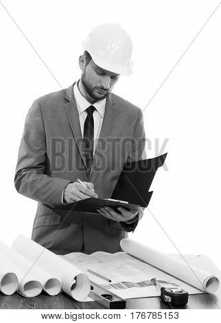 Noting carefully. Monochrome shot of a professional constructionist writing on his clipboard profession notes info developer businessman builder foreman architect urban profession occupation concept