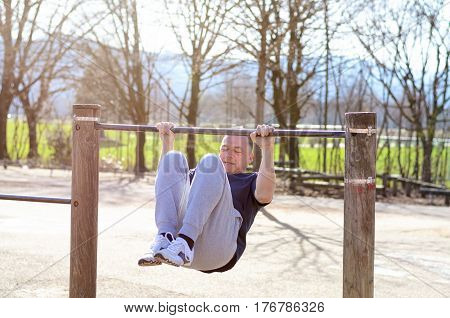 Middle-aged man working out on a horizontal bar in an outdoor sports area in rural countryside in an active lifestyle and wellness concept