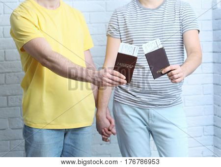 Happy gay couple with passports and tickets on brick wall background