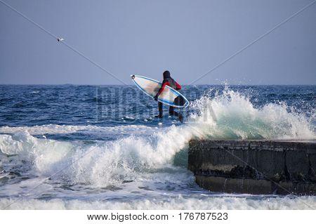 Surfer jumping into water. He is wearing a wetsuit in winter. waterproof suit