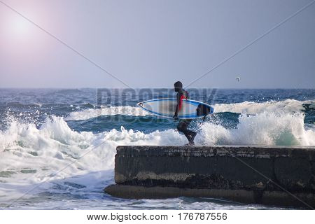 Surfer runs into water wearing a wetsuit. Wave splash. waterproof suit