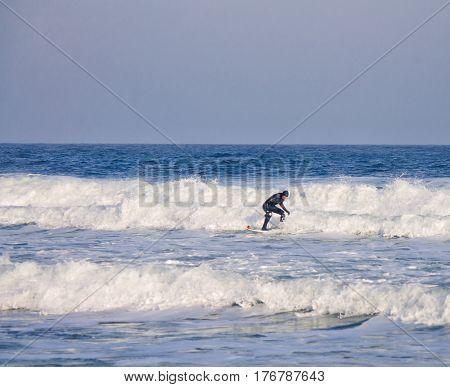 surfer rides waves in the water wearing a wetsuit. Wave splash. waterproof suit