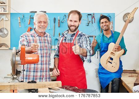 Successful luthiers holding thumbs up at artisan's workshop