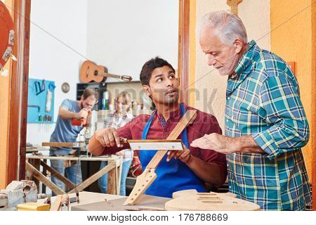 Young man learns from luthier master in saw lesson while making a guitar