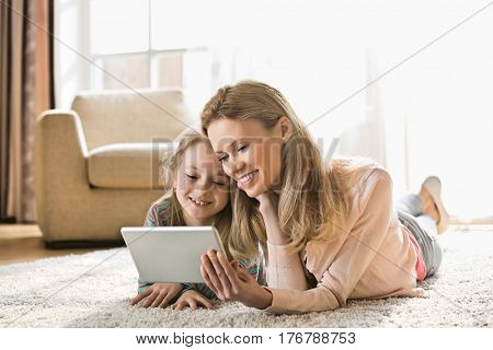 Mother and daughter using digital tablet on floor at home