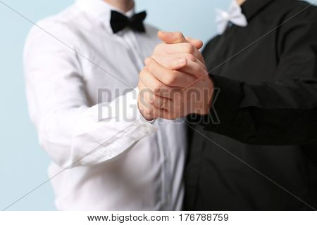 Happy gay couple dancing against color background