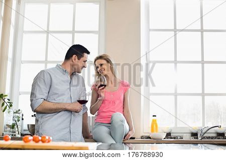 Happy couple looking at each other while drinking red wine in kitchen