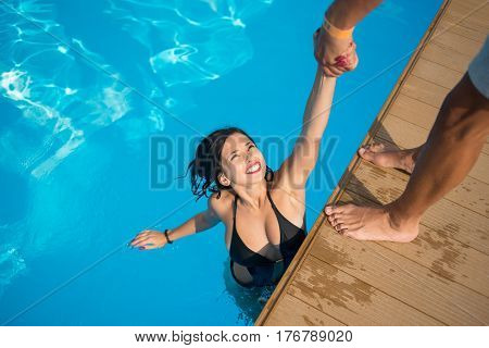 View From Above Of Attractive Girl In The Swimming Pool Holding A Man's Hand Trying To Get Out At Re