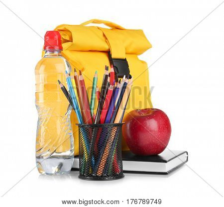 Holder with colorful pencils, bottle of water and lunch bag on white background